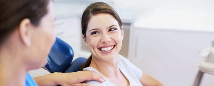 A happy woman smiling look up at her dentist after undergoing a teeth whitening procedure
