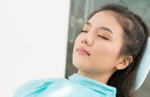 An Asian woman that is current asleep from dental sedation.