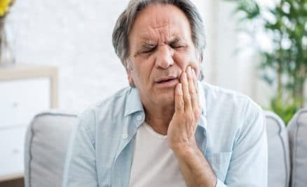 man suffering tooth pain