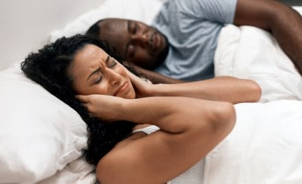 couple sleeping in bed with partner snoring