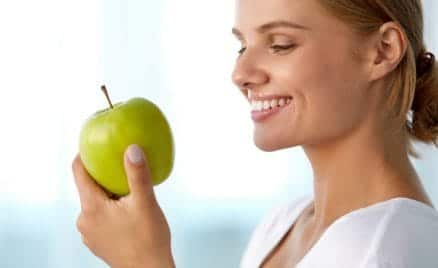 woman eating green apple, healthy smile