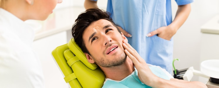 Young man holding cheek in chair at dentist, having toothache.