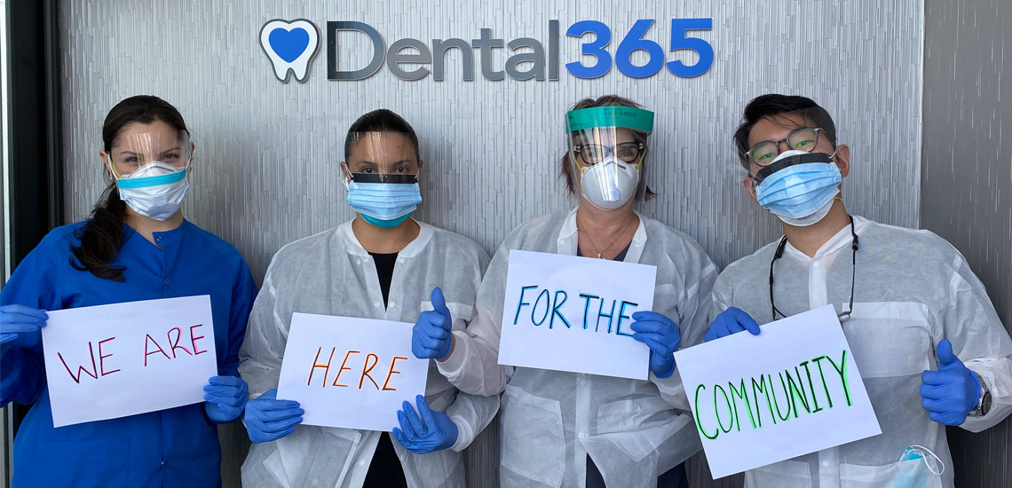 Four Dental365 employees holding signs that say We are Here for the Community