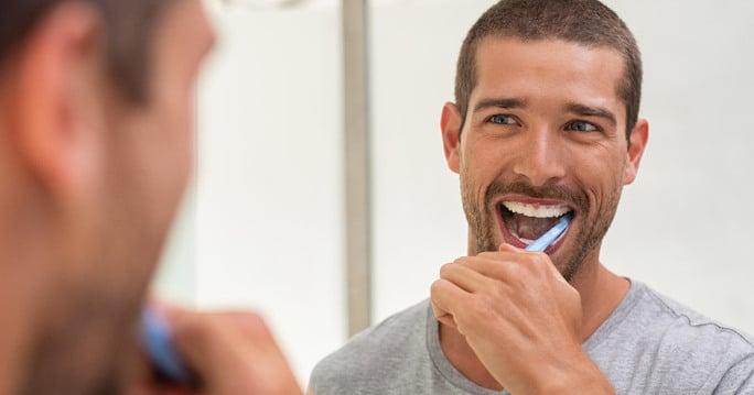 Man looking in mirror brushing his teeth
