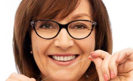 senior woman cleaning her teeth by dental floss