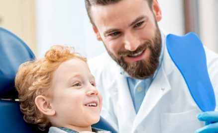 Young excited boy at the pediatric dentist or pedodontist office looking at his teeth