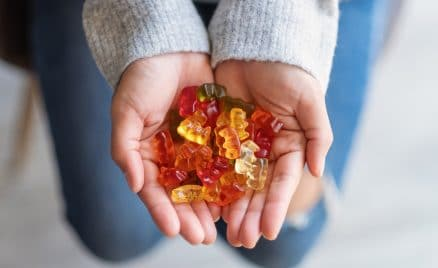 Closeup image of a woman holding colorful jelly gummy bears in hands